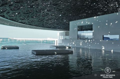 Modern buildings with water and a honeycomb roof, sunlight piercing through. Louvre Abu Dhabi.