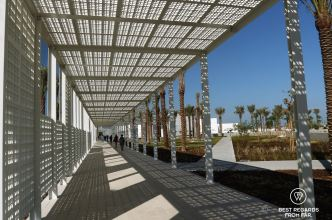 White metal alley lined with palm trees leading to the entracne of Louvre Abu Dhabi, UAE.