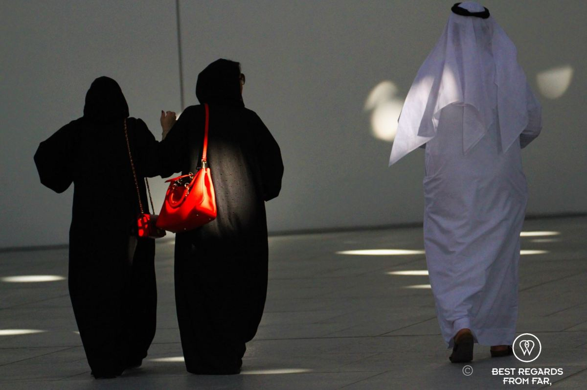 Two women walking wearing black burkas with red handbags and a man walking with a white thawb.