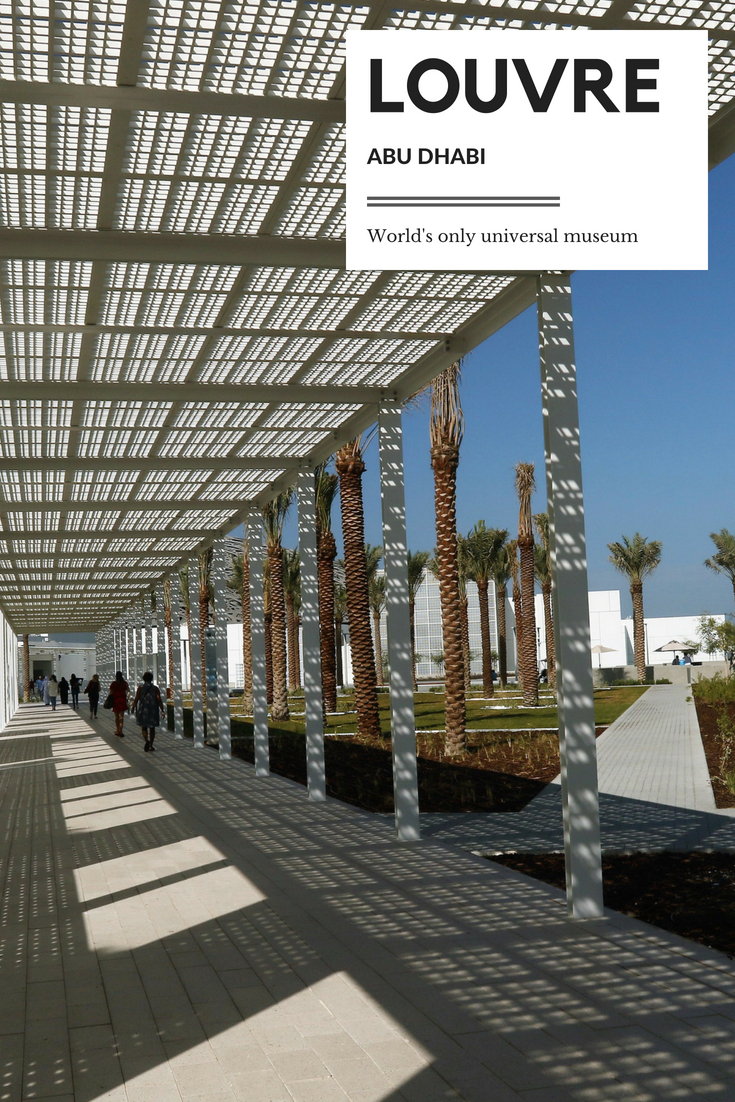 Modern entrance of the Louvre Abu Dhabi, palm trees and blue skies.