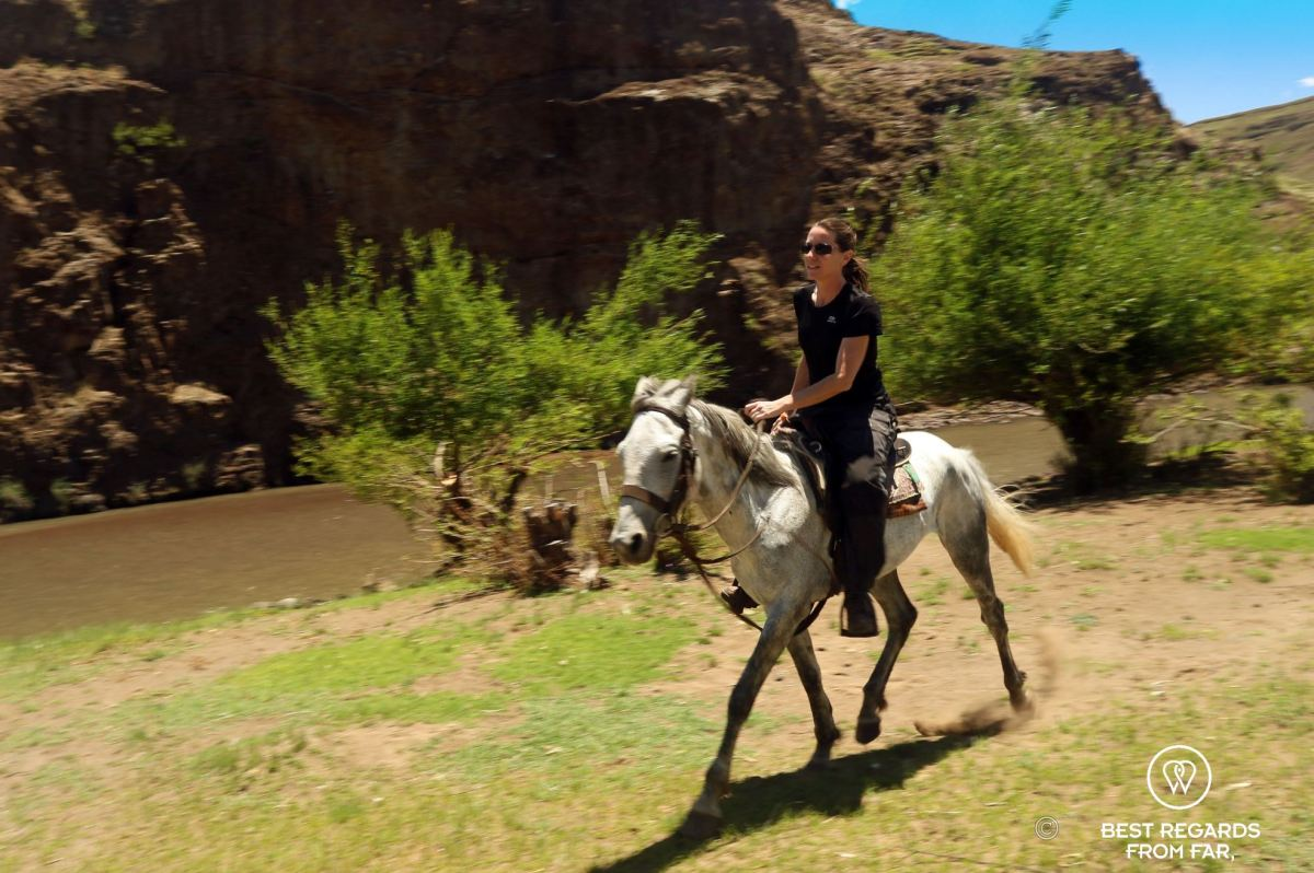 Writer Claire Lessiau galloping along the Orange River in Lesotho.