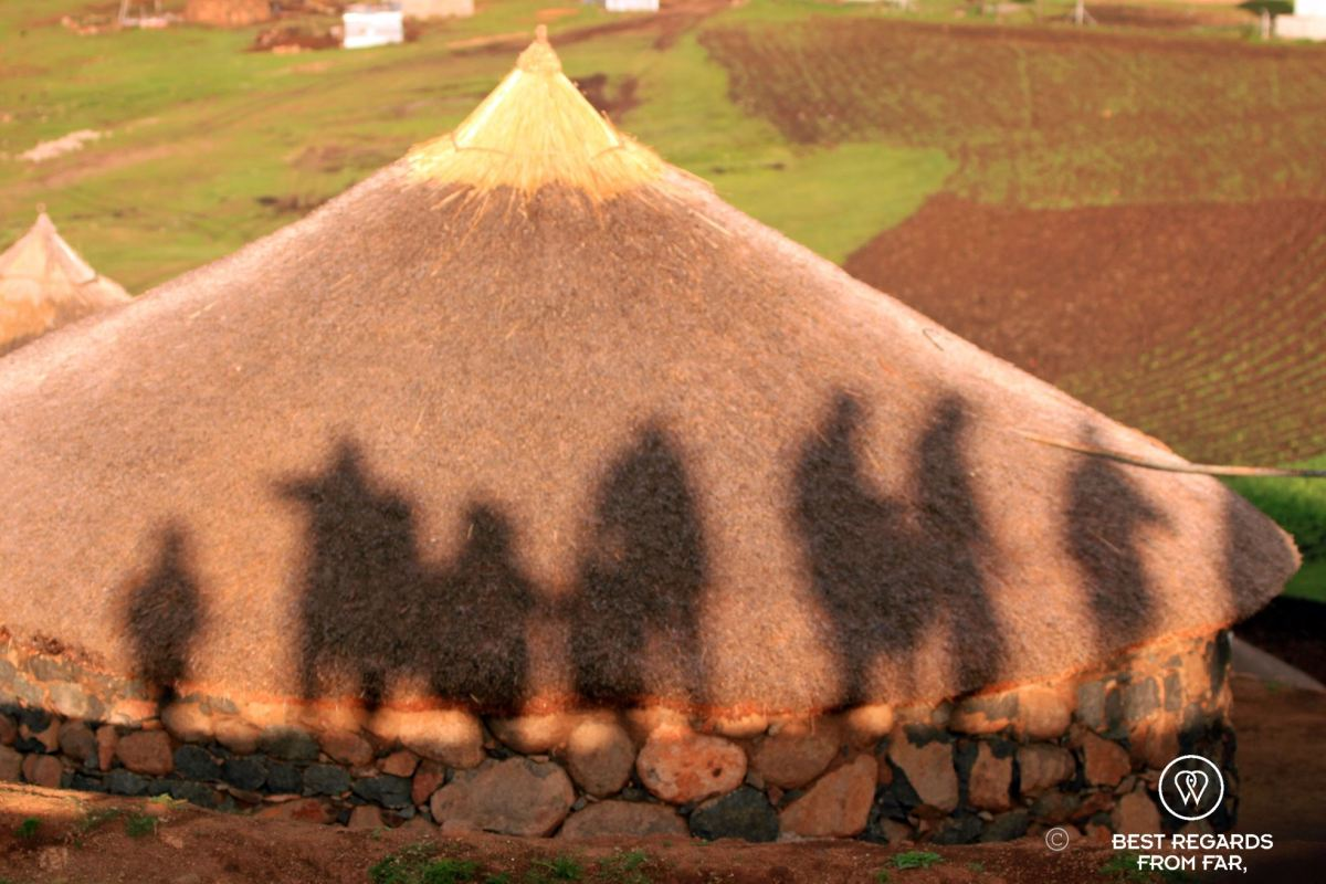 Shadows of Basotho people on the roof of a rondavel at sunset, Lesotho.