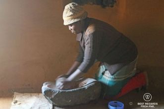 Basotho woman using a grinding stone to make homemade beer in Malubelube, Lesotho.