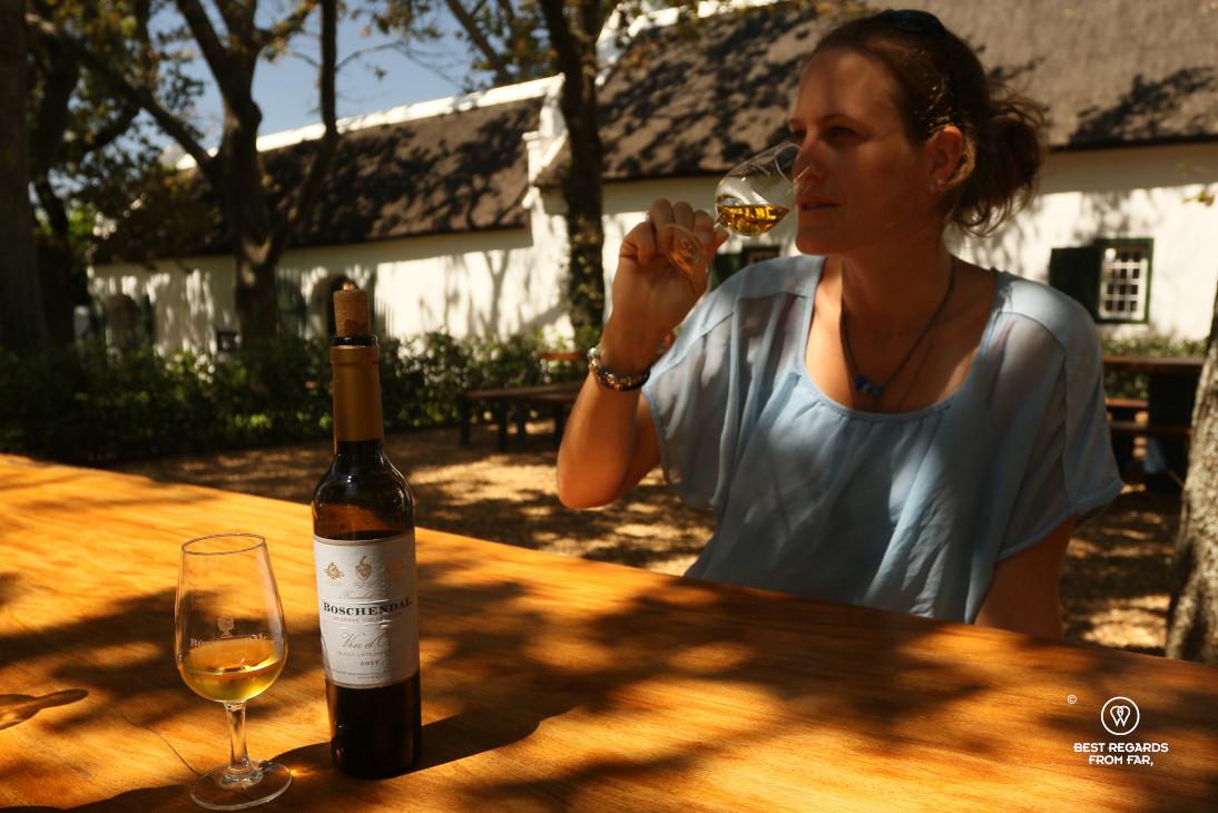 Woman tasting the Boschendal dessert wine on the estate under oak trees, Franschhoek, South Africa.