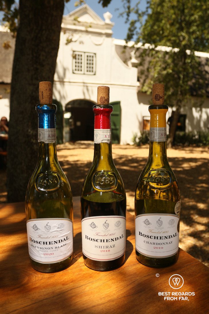 3 bottles of wine at Boschendal with a historic Cape Dutch mansion in the background, Franschhoek, South Africa.