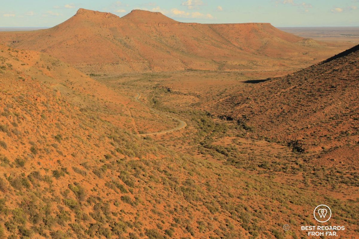 Red dry and hilly landscape with one road going through, Karoo NP, South Africa.