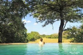 Woman observing wildlife from the pool, &Beyond Phinda Private Game Reserve Forest Lodge, South Africa.