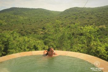 Woman in a private pool overlooking the green hills of Phinda Private Game Reserve, South Africa.