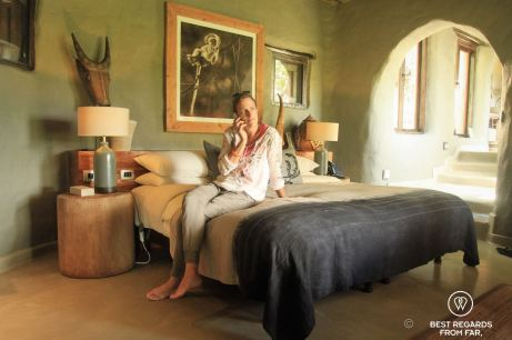 Photographer Marcella van Alphen on a bed in a luxurious room making a phone call.