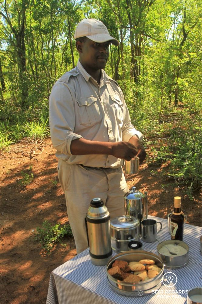 Ranger in khaki uniform and cap preparing drinks at a table with cookies in the bush.