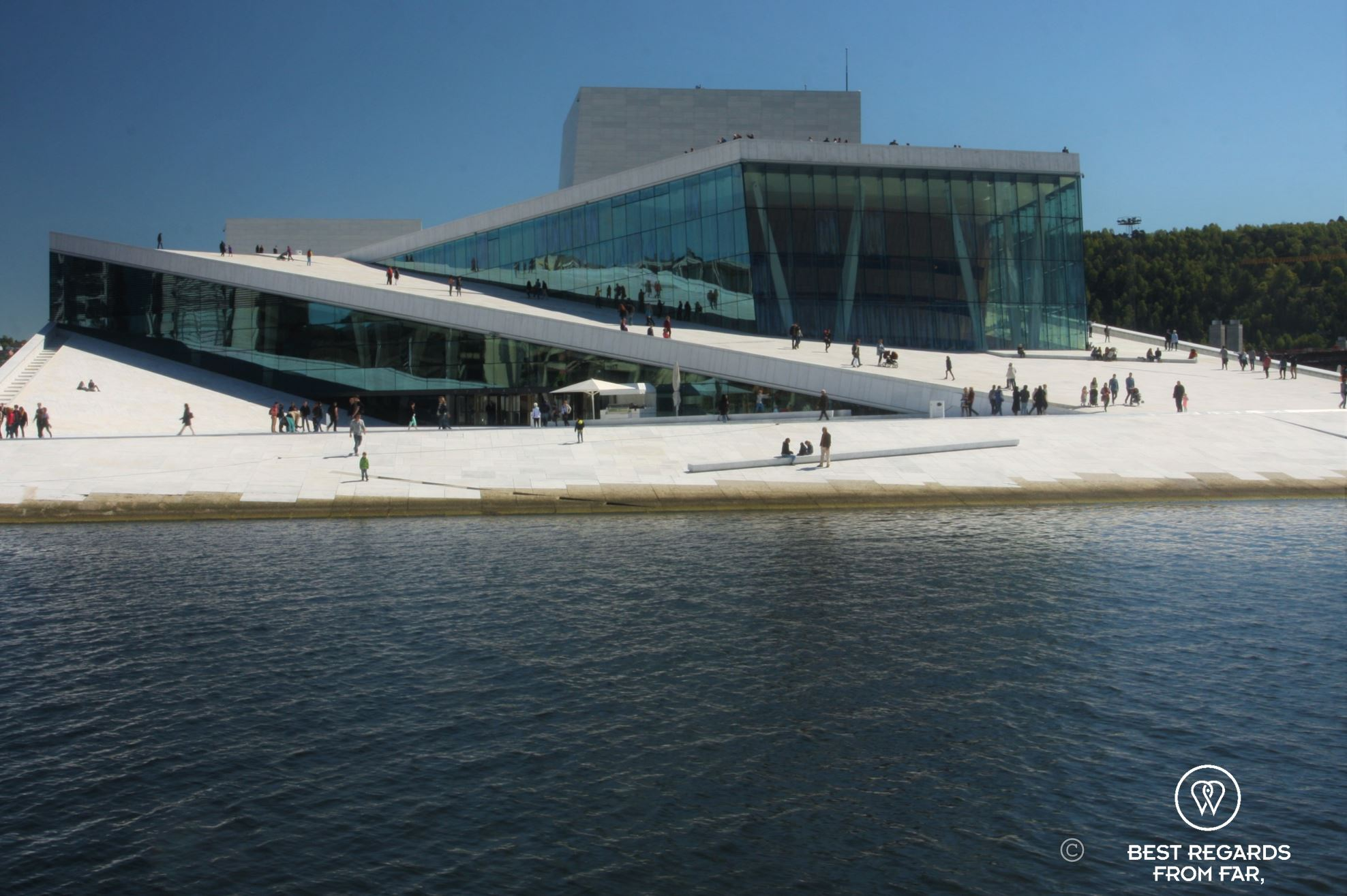 Modern building of the Oslo Opera House, white marble rising out of the water with people walking on its roof.