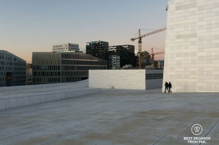 Two people walking on the white marble rooftop of the Oslo Opera House with modern buildings at the background.