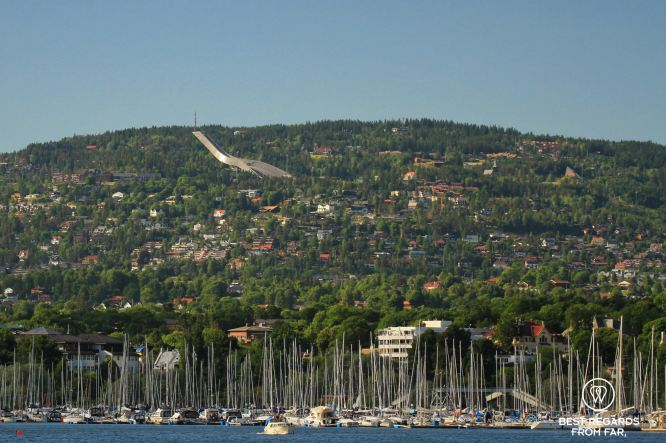 Blue water with a harbour full of sail boats, green mountain with a large ski jump, Oslo, Norway.