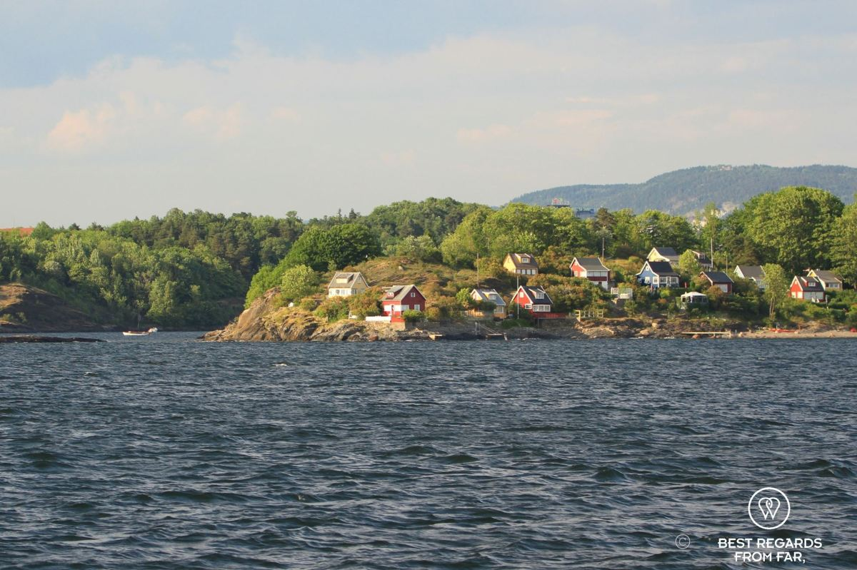 Small island with wooden houses seen from the water. Bleikoya, Oslo, Norway.