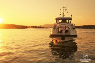 White ferry boat with two people on board on a body of water at sunset.