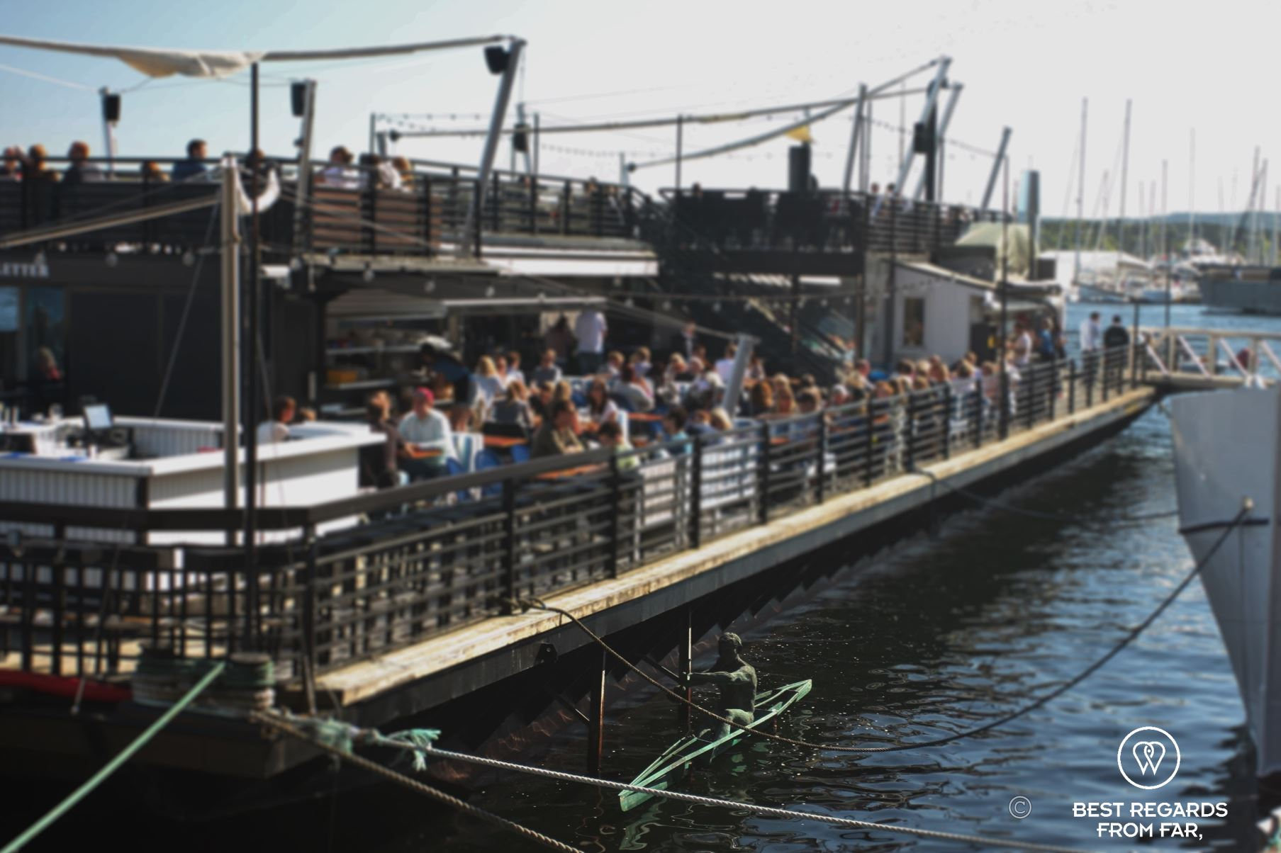 People having drinks in the sun on a large pontoon in the harbour of Oslo, Norway.