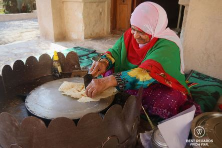 Woman baking Kuboos, crispy flat bread with honey in the Nizwa Fort, Oman