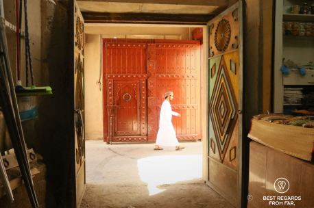Young man walking by the souq, Nizwa, Oman