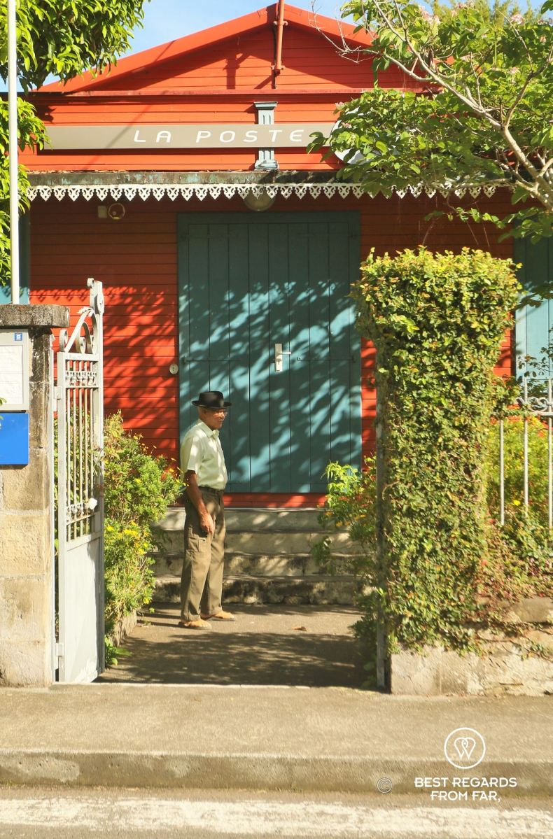 An old local man in front of the colorful colonial post office in Hell Bourg in the Salazie amphitheater on the exclusive multiday hike through the 3 cirques, Réunion Island.