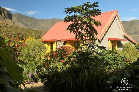 Gîte of the Ilet à Bourse in Mafate: a colorful house among tropical flowers and green mountains, on the exclusive multiday hike through the 3 cirques, Réunion Island.