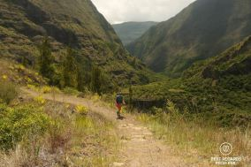 Hiker walking on the trail in Mafate on Reunion Island among the green mountains.