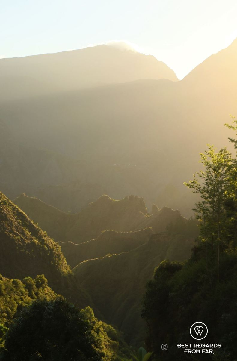 Sunrise in the Mafate amphitheater and its layers of green mountains during an exclusive multiday hike through the 3 cirques, Réunion Island.