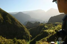 A hiker in the evening sunlight overlooking layers of mountains at Ilet des Orangers in Mafate during an exclusive multiday hike through the 3 cirques, Réunion Island.