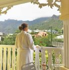 A guest at the balcony of the colonial Tsilaosa Hotel, enjoying a morning French-pressed coffee and looking at the view on the mountains of Cilaos, Réunion Island.