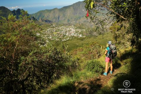 A multiday hiker looking at a view on the city of Cilaos on the exclusive hike through the 3 cirques, Reunion Island.
