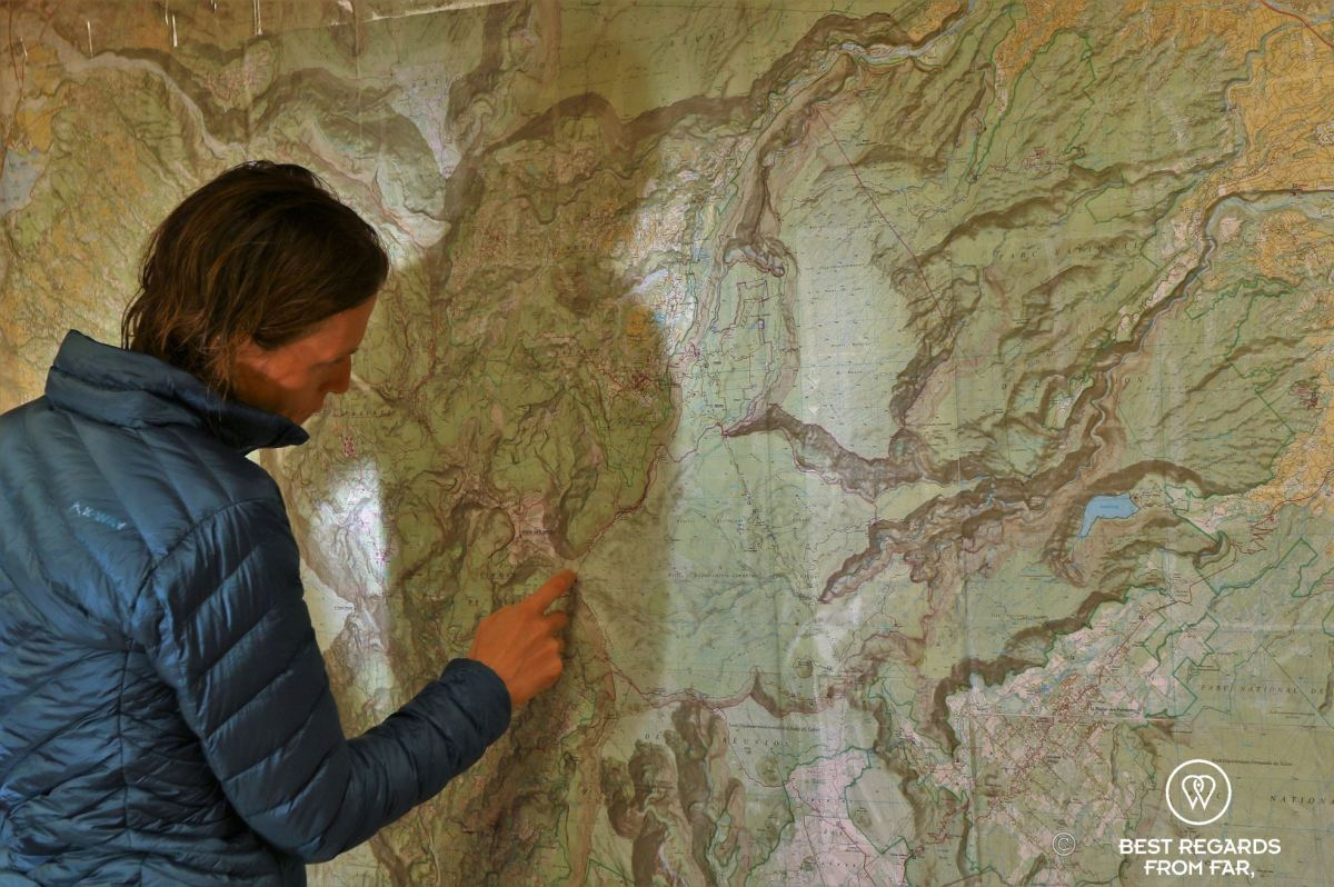 Hiking in technical clothes planning the exclusive multiday hike through the 3 cirques, Réunion Island, on a large wall map of the island.