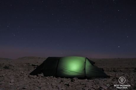 A lit mountain tent at night under the stars on the Selma Plateau high in the eastern Hajar Mountains of Oman.