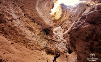 Woman climbing up from the Seventh Hole Cave in Oman, using roping techniques.