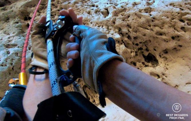 Action shot of the hands of a caver going up the Seventh Hole Cave in Oman operating the technical caving and roping gear.