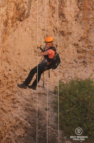 Woman in full caving gear free abseiling down a rope to explore the Seventh Hole Cave in Oman.