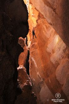One person free abseiling down a rope to explore the Seventh Hole Cave in Oman. The abseil is so long (120 meters) that the caver looks tiny among the rocks.