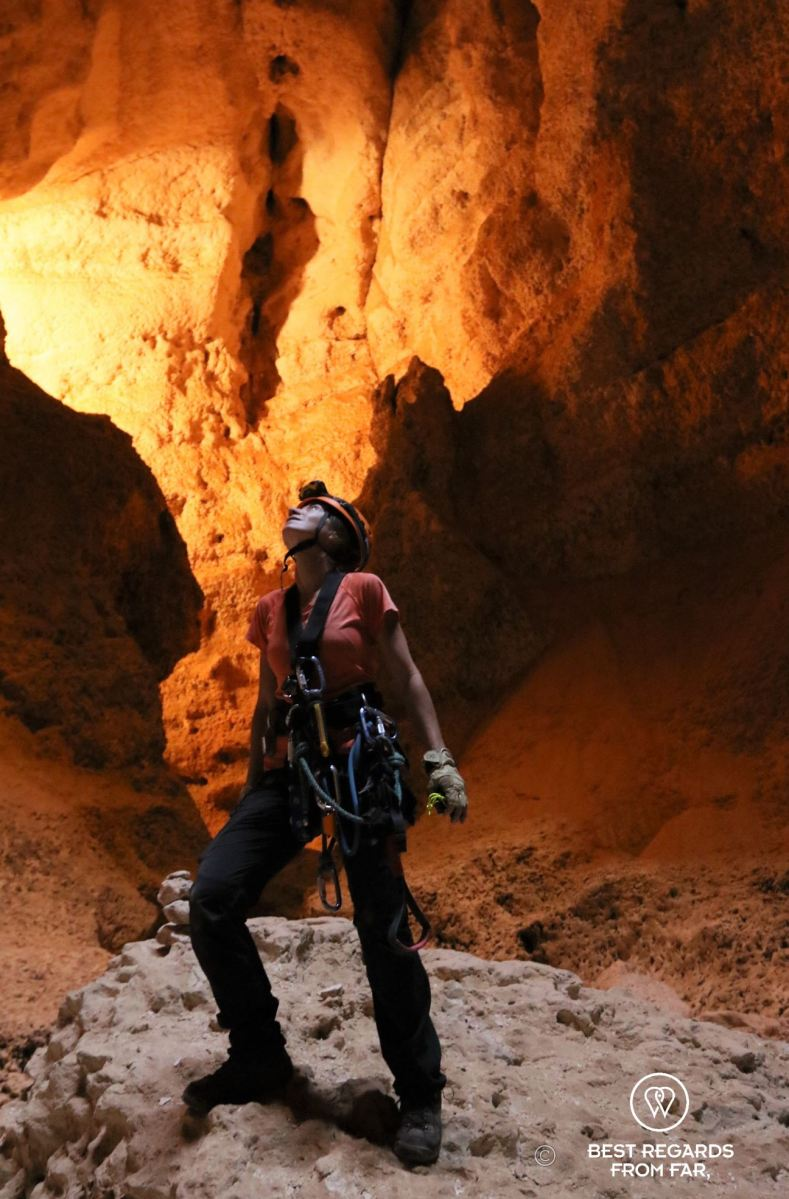 A woman in full technical caving gears looking up from the bottom of the Seventh Hole Cave in Oman.
