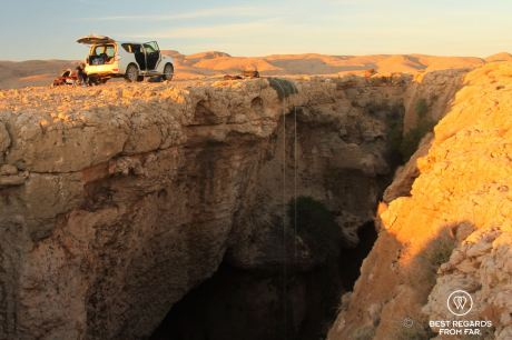 Setting up for the Seventh Hole caving expedition, Oman: ropes hanging into the cave from a 4x4 at sunrise.