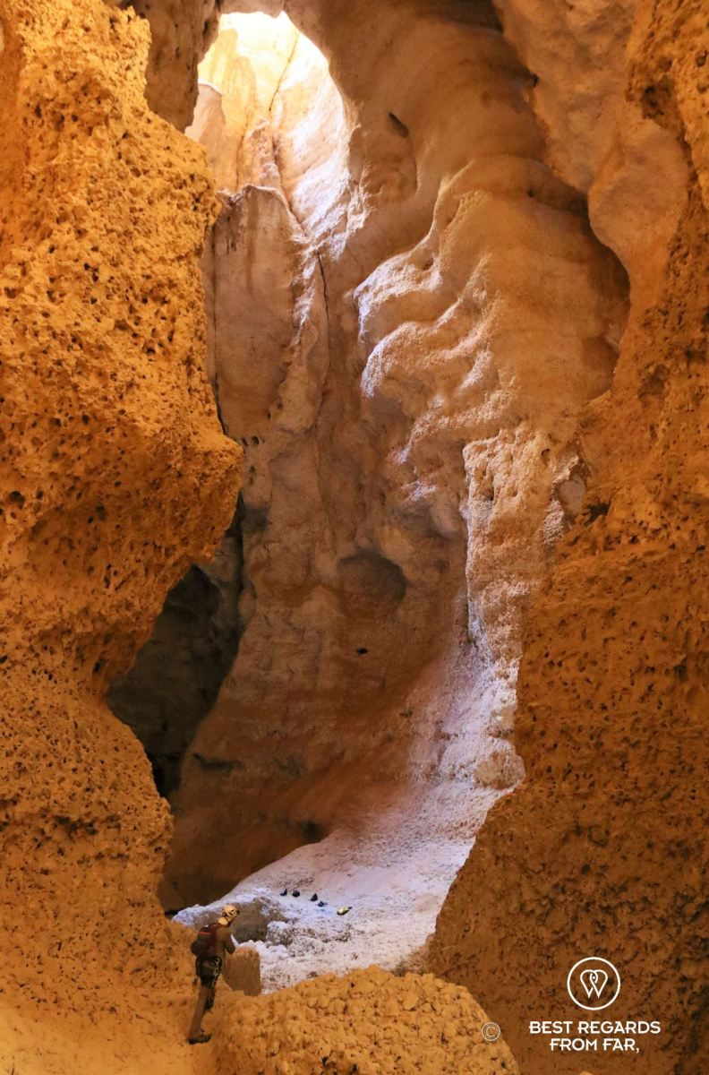 A person caving at the bottom of the huge Seventh Hole Cave in Oman.