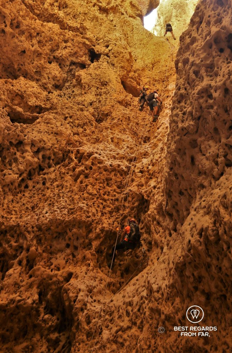 Several people climbing up along rocks on different rope sections from the bottom of the Seventh Hole Cave in Oman.