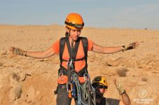 Final gear check on photographer Claire Lessiau by expert caving guide Justin Hall before caving the Seventh Hole, Oman.