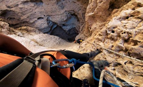 Caver on ropes in gull technical gear looking down: two other cavers are climbing back up from the Seventh Hole Cave in Oman.