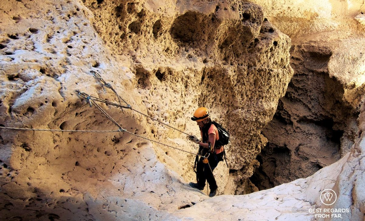 Photographer Claire Lessiau climbing up from the Seventh Hole Cave in Oman, using roping techniques.