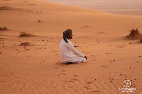 Praying at sunset in the desert, Oman
