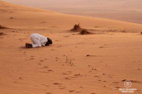 Praying at sunset in the desert, Oman