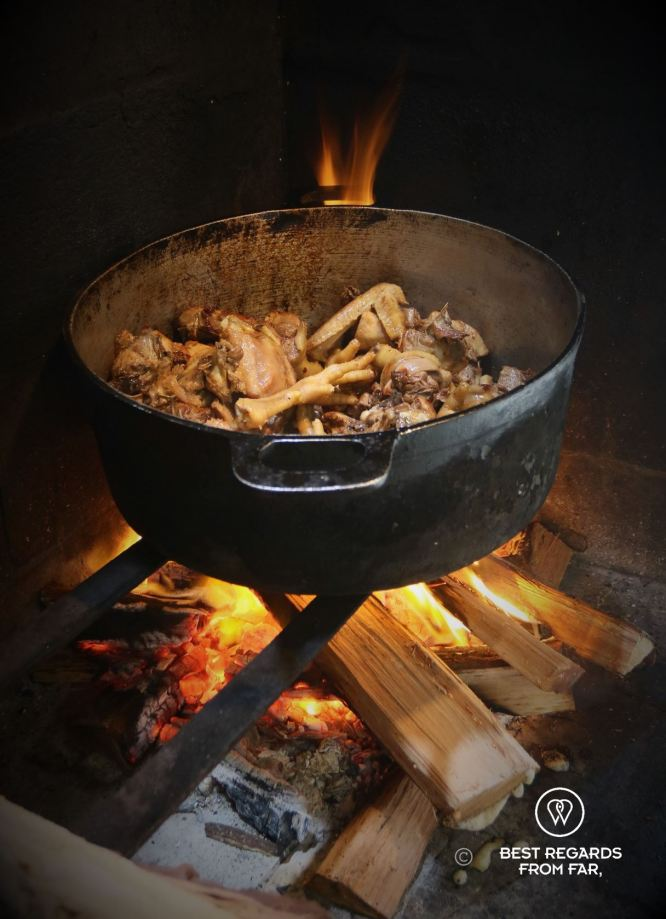 Chicken feet cooking on a woodfire in a cast iron pan, Reunion Island