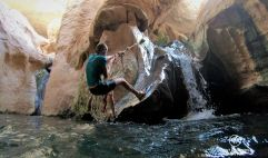 Marcella climbing up the waterfall in Wadi Shab, Oman