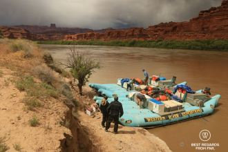 Western River Expeditions rafts anchored along the bank of the Colorado River during the Cataract Canyon rafting trip. Threatening sky in the background.