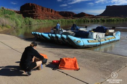 Adventurer packing a large waterproof bag on the bank of the river with the Western River Expeditions rafts waiting to go on the Colorado River, Utah, USA.