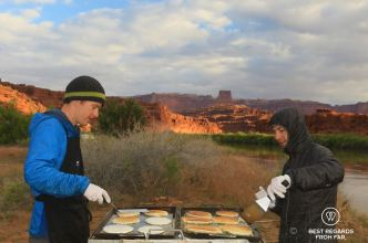 River guides baking pancakes at sunrise on the banks of the Colorado River, during the Cataract Canyon rafting expedition with Western River Expeditions.