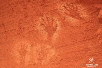 Ancient rock art depicting hands on the red rocks by the Colorado River.